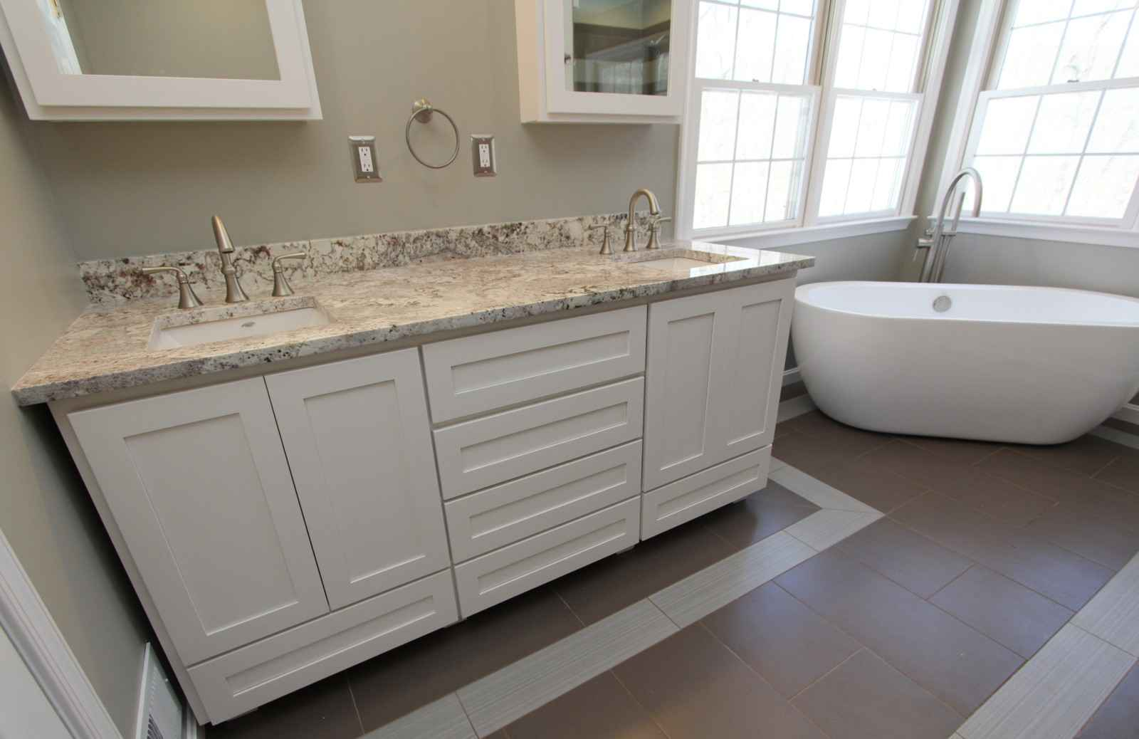 remodeled bathroom with dual sink and freestanding tub